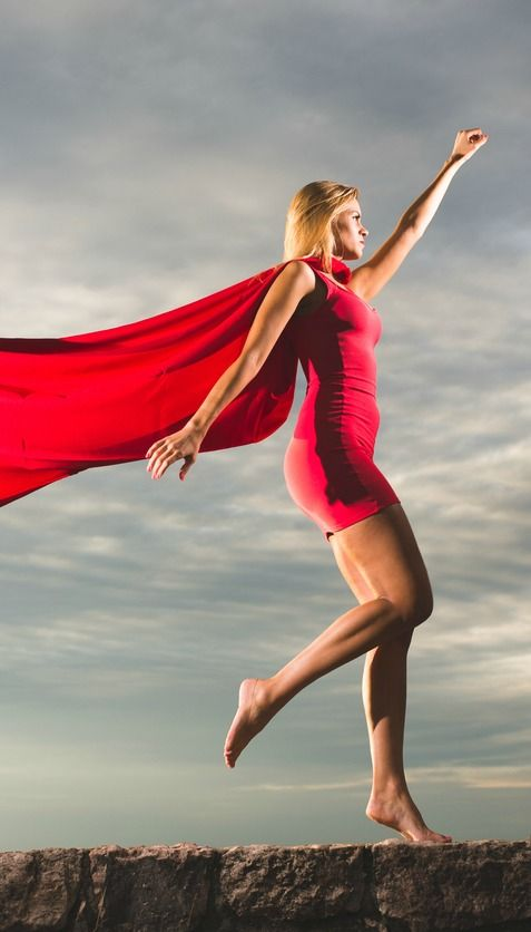 girl in red dress and cape on a wall