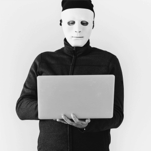 a guy with a mask on standing working on a computer