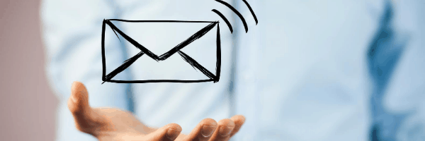 a guys hand holding an email symbol
